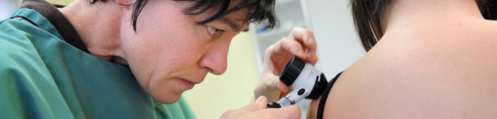 Un médecin auscultant les grains de beauté d'une patiente (illustration)