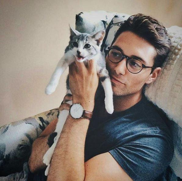 Un joli brun, ses lunettes et son chaton en colère