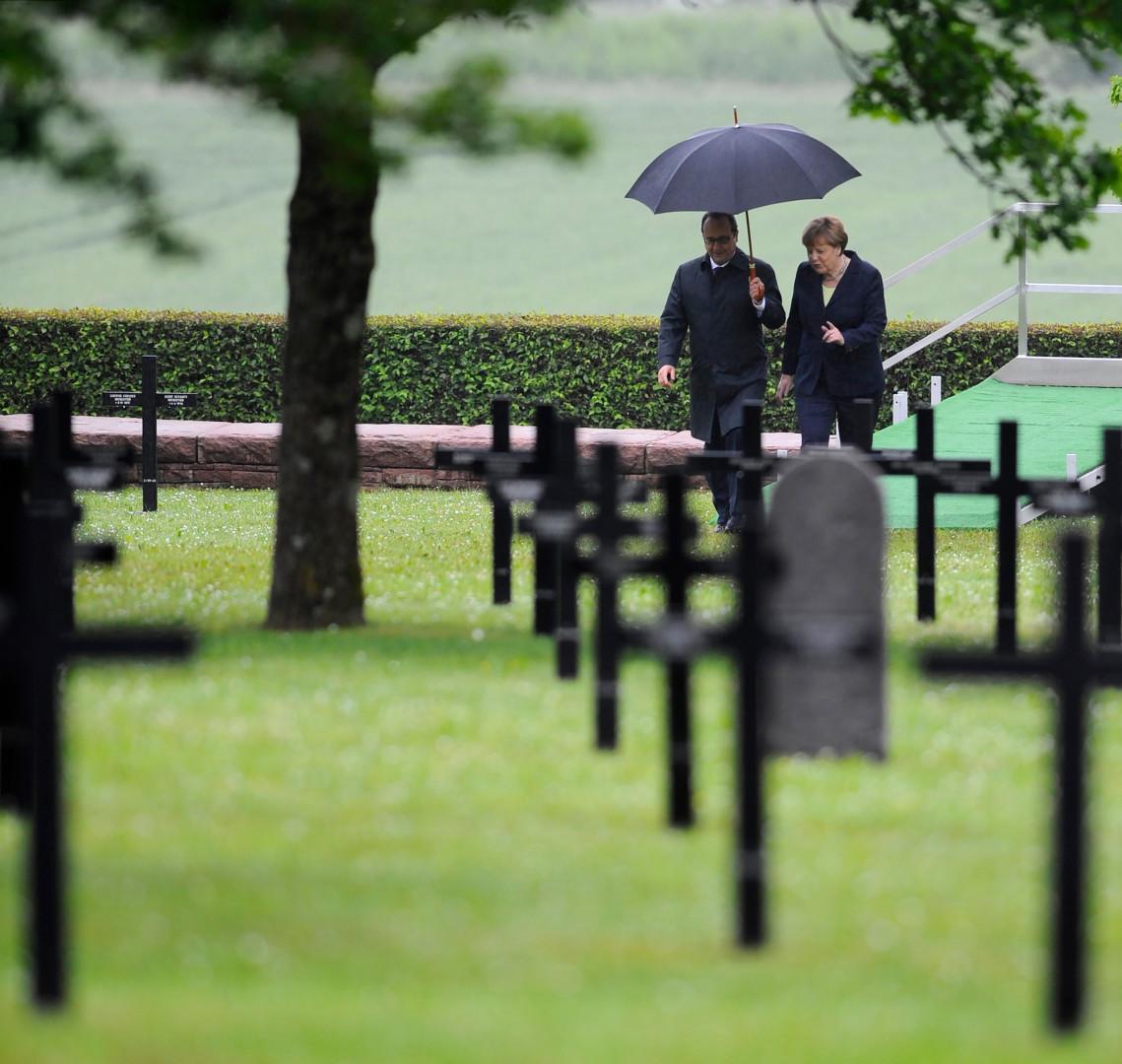 Sous une pluie continue, François Hollande a tenu à abriter lui-même Angela Merkel sous son parapluie pendant une cérémonie sous le signe de l'amitié franco-allemande.