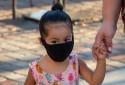 Une petite fille avec un masque sur le chemin de l'école (Image d'illustration).