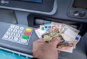 Un homme retire de l'argent d'un distributeur automatique de billets