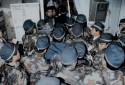 La police anti-émeute japonaise s'engouffre à l'entrée de la propriété de la secte Aum Supreme Truth à Osaka le 24 mars 1995.