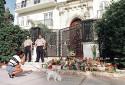 Des agents de sécurité privés se tiennent devant la maison du designer italien Gianni Versace le 16 juillet 1997 à Miami Beach, en Floride, alors qu'une femme promenant son chien s'arrête pour prendre une photo de l'endroit où Versace a été tué.