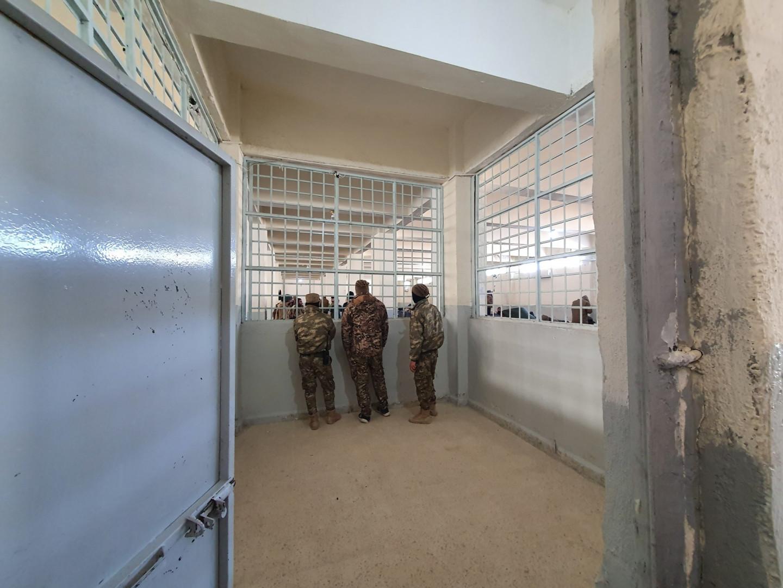 """Des gardes masqués inspectent la section """"hôpital"""" de la prison."""