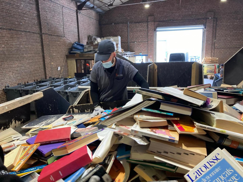 Dans l'entrepôt les salariés trient papiers, documents et livres récupérés dans la région.