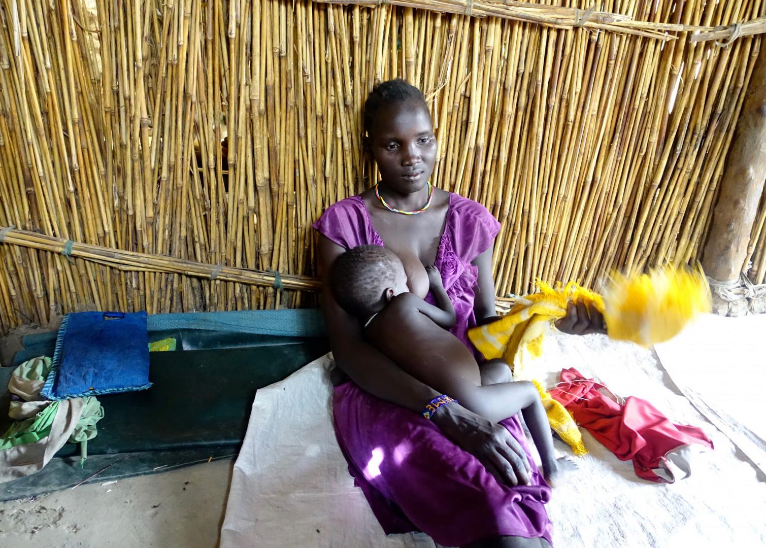 Une mère nourrit son enfant au sein dans son habitation.