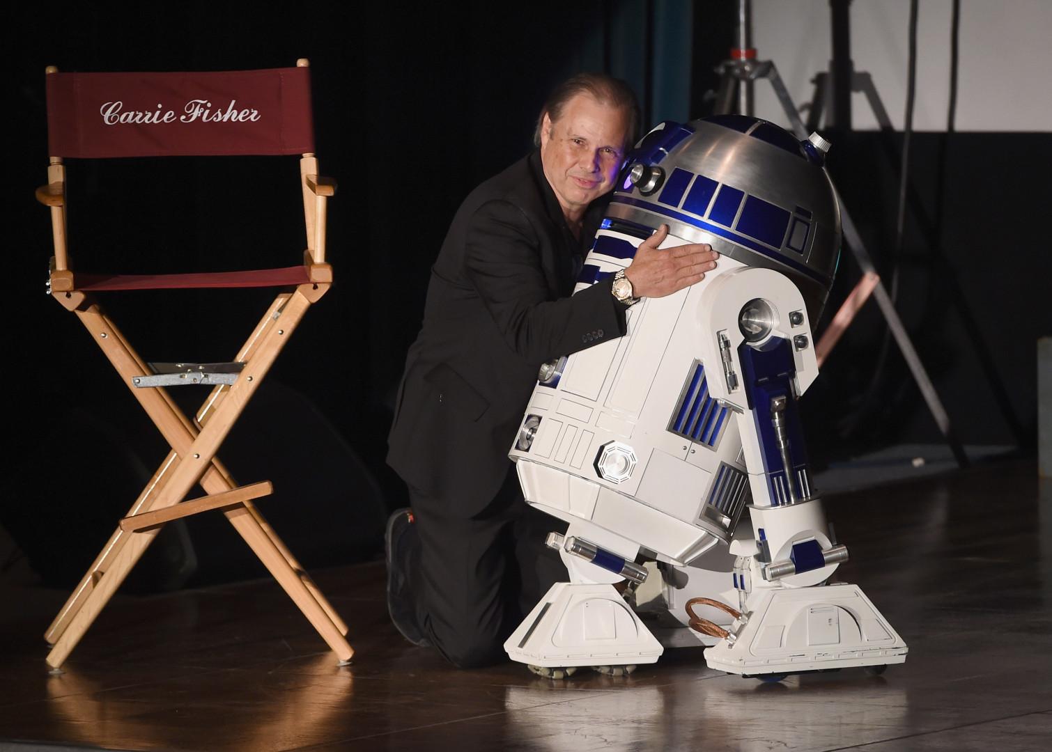 """Todd Fischer, frère de Carrie Fischer, pose avec R2-D2, robot vedette de la saga """"Star Wars"""""""