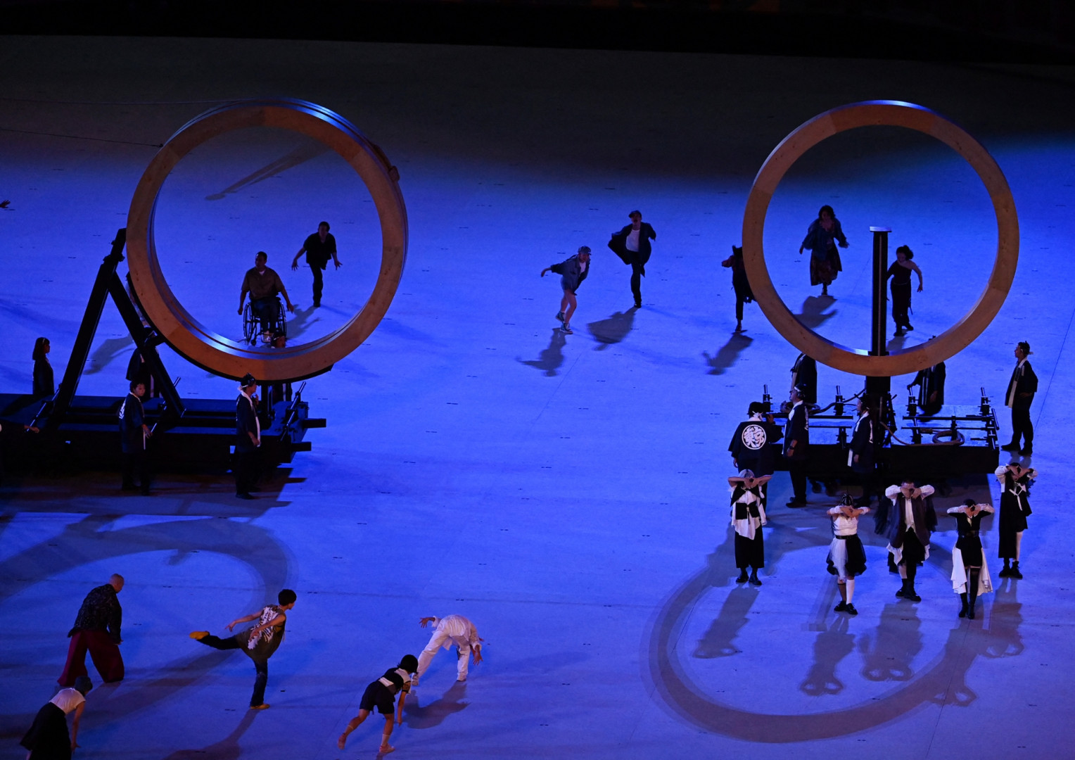 Les cinq anneaux olympiques arrivent séparément sur des chariots de bois