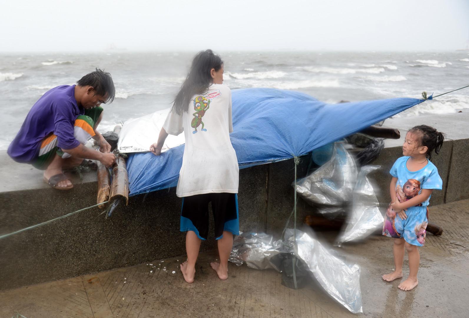 Une famille tente de se faire un abri alors que le typhon Koppu frappe les Philippines, le 18 octobre 2015.