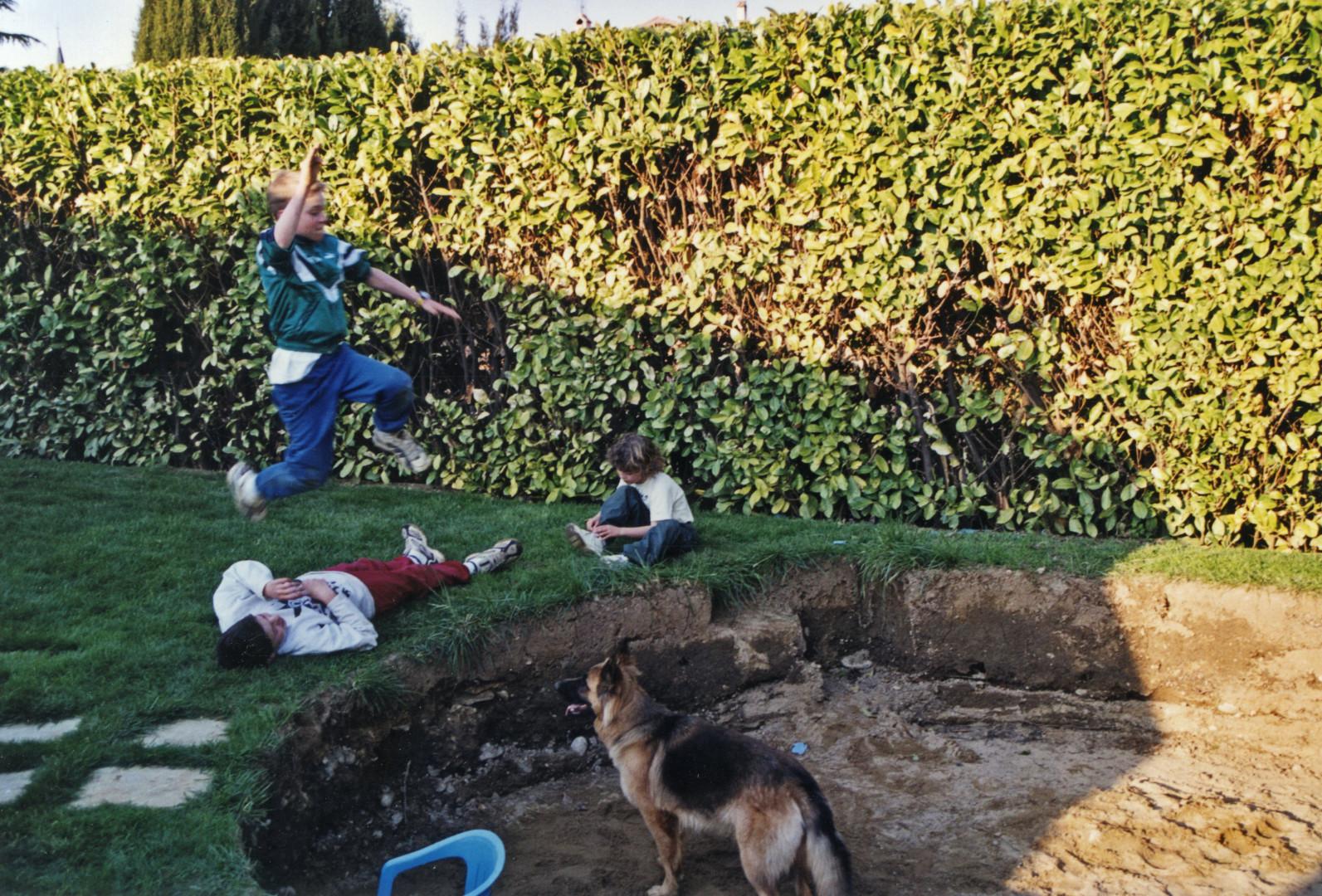 Concours de saut en longueur improvisé dans le jardin sous le regard du chien