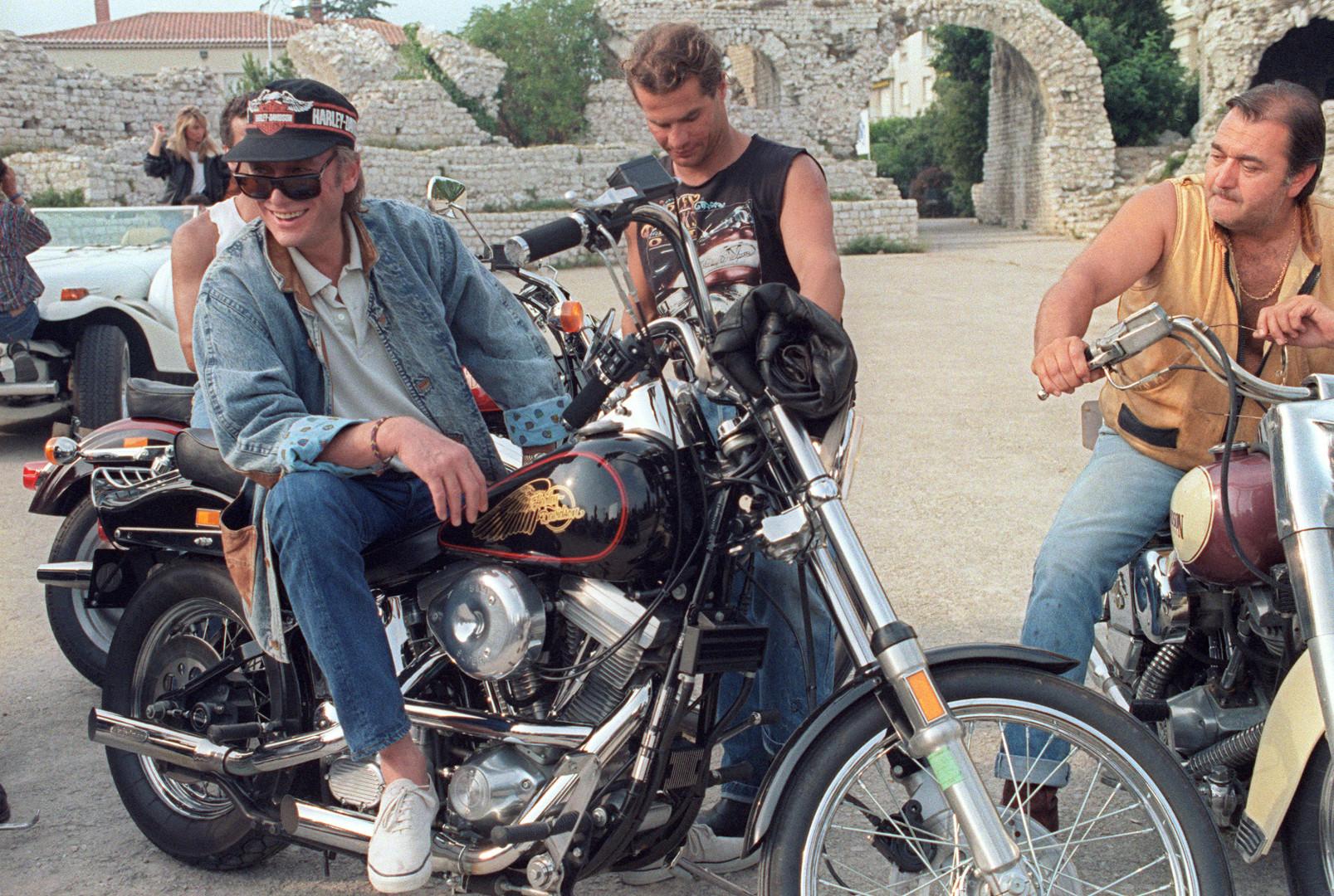 9 août 1987 : Johnny assis sur une Harley-Davidson à Nice lors du tournage d'un film publicitaire