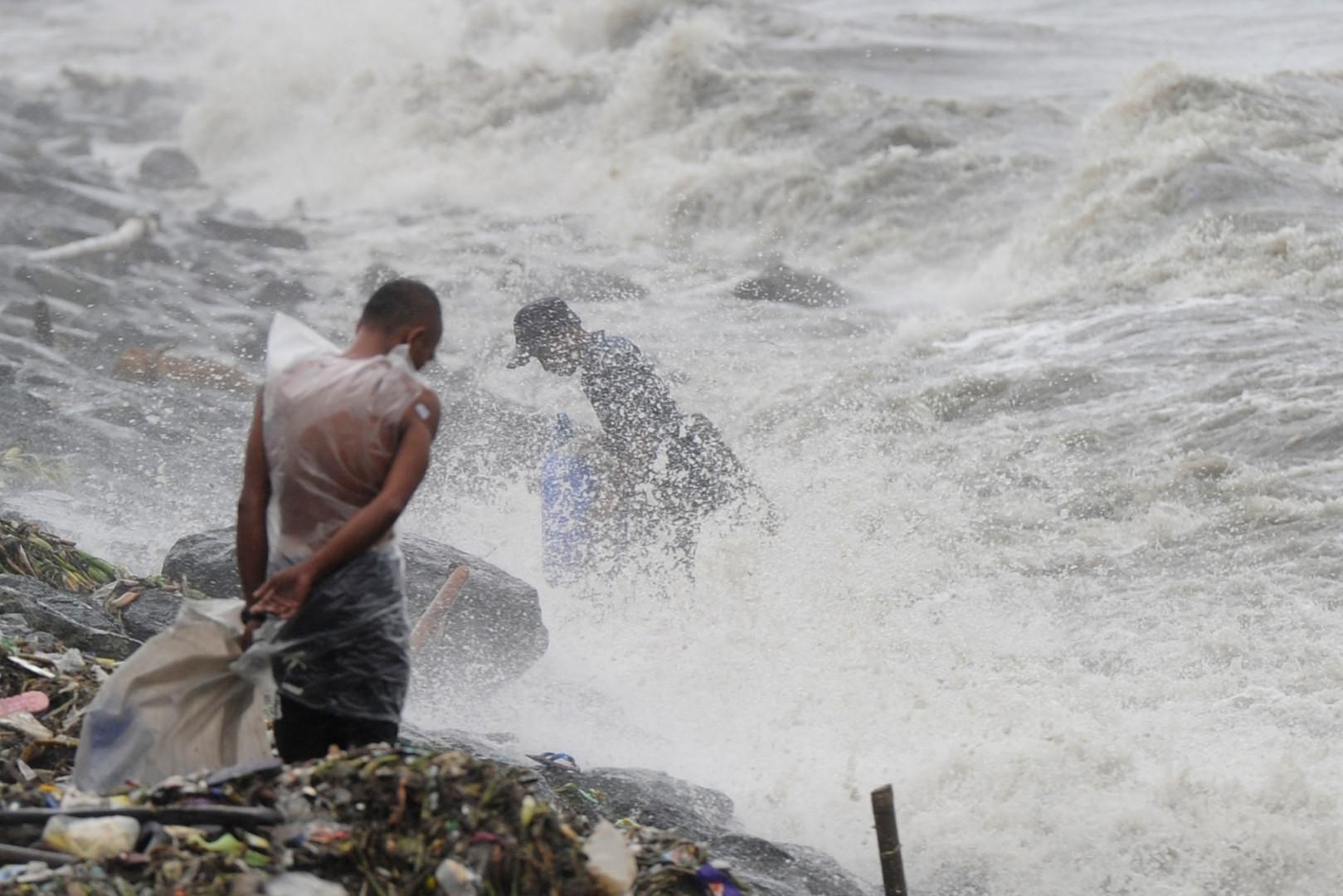 Des Philippins bravent la pluie et le vent causés par le typhon Koppu dans la province Aurora, au nord de Manille, le 18 octobre 2015.