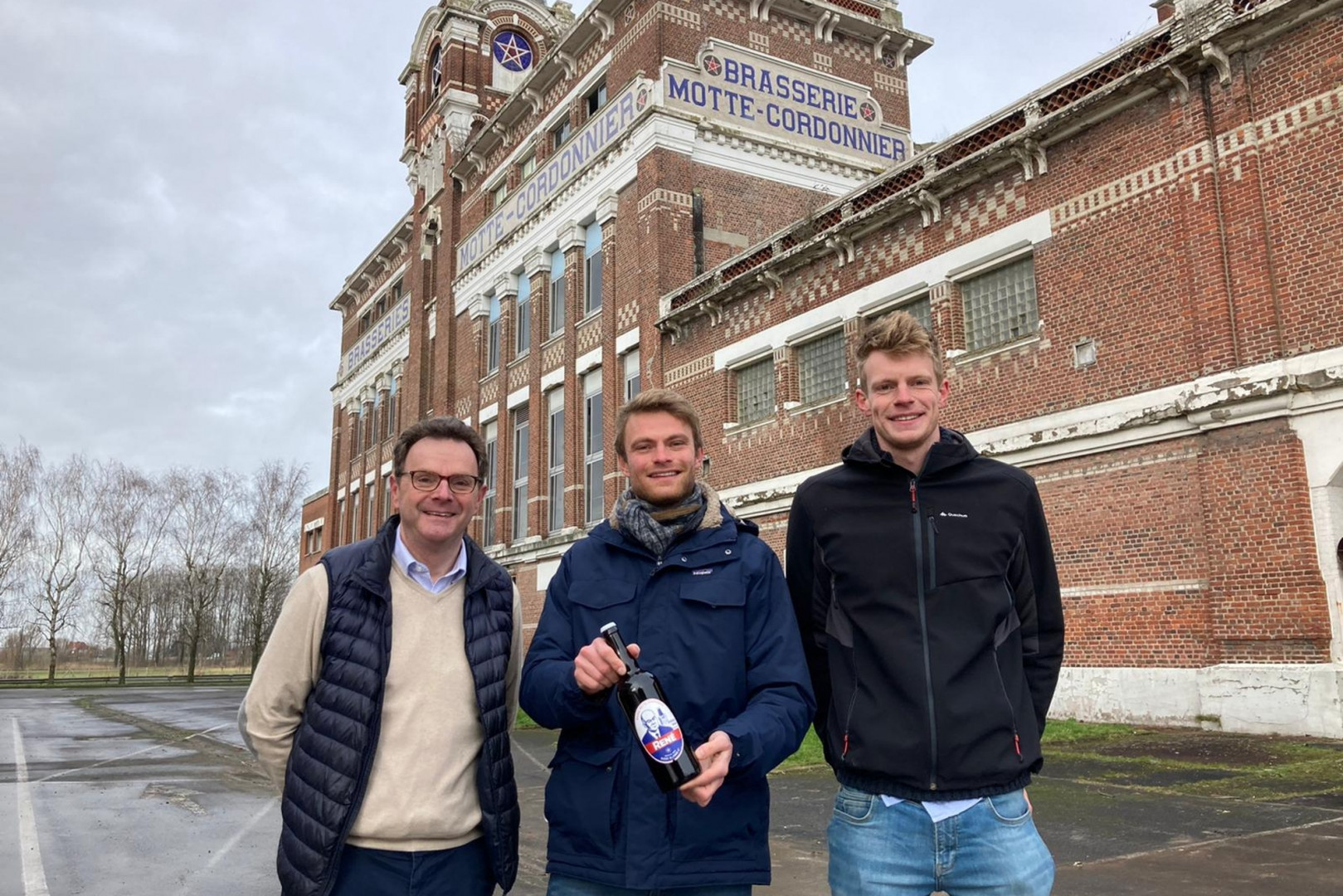 """Frédéric Motte, Gilles et Henry, ses deux neveux, devant la brasserie, avec une des bouteilles """"René"""" du nom de l'arrière grand-père bâtisseur."""