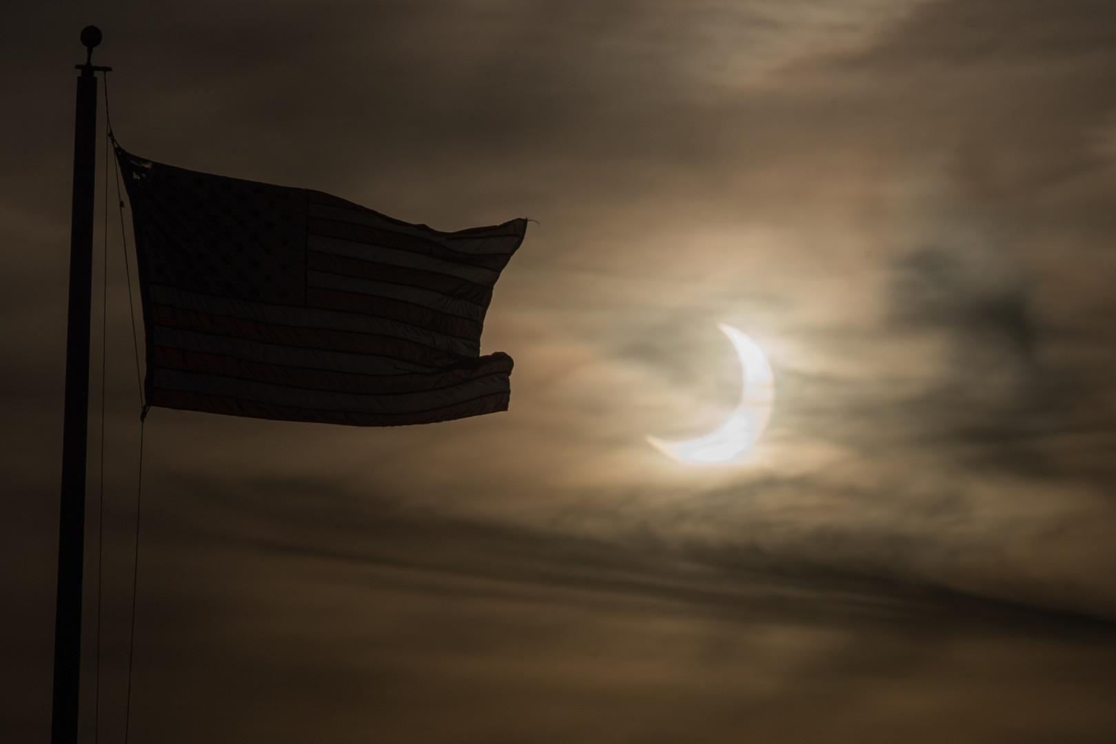 Un soleil éclipsé se lève à côté d'un drapeau le 10 juin 2021 à Scituate, Massachusetts.