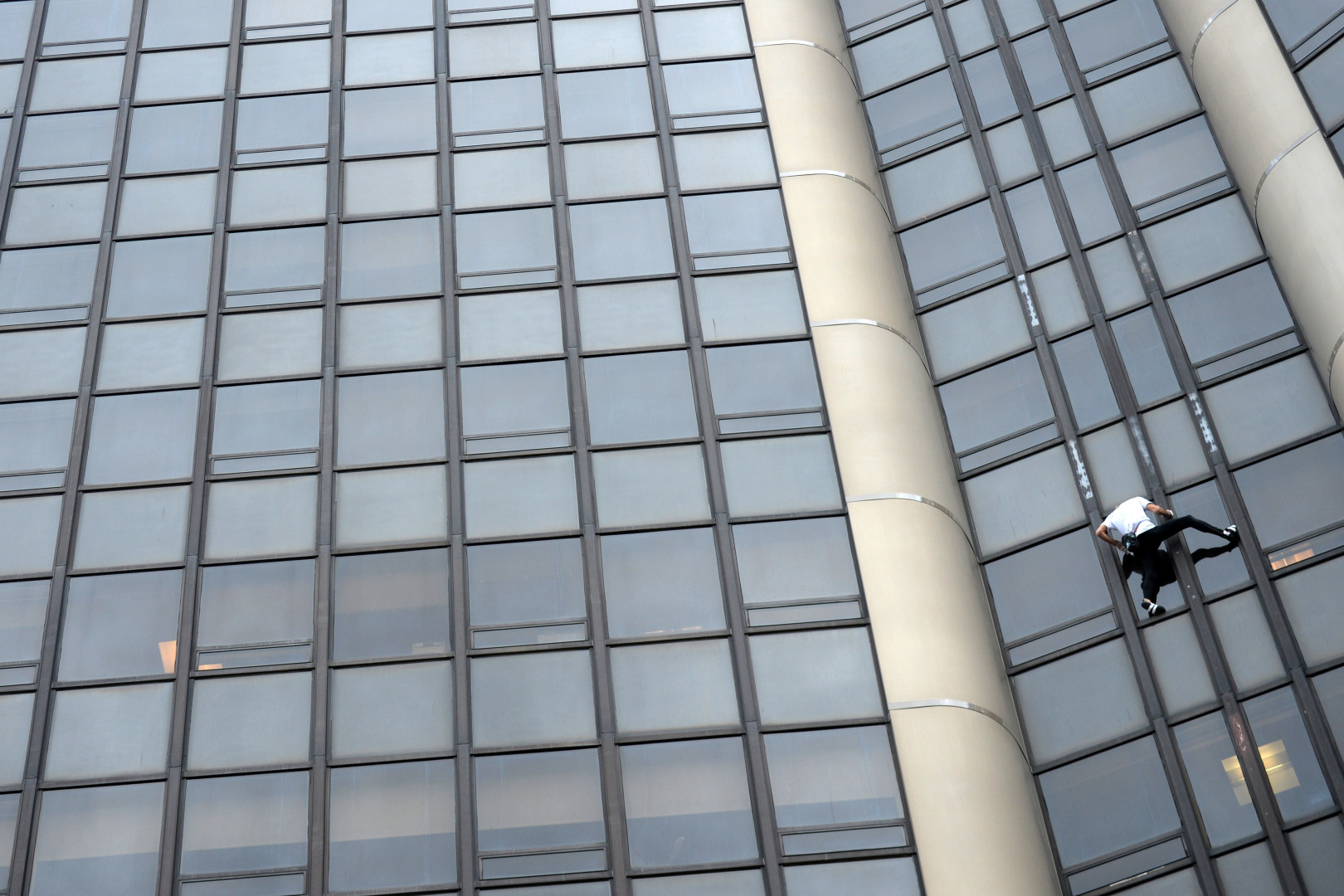 Alain Robert grimpe à mains nues et sans harnais la tour Montparnasse.