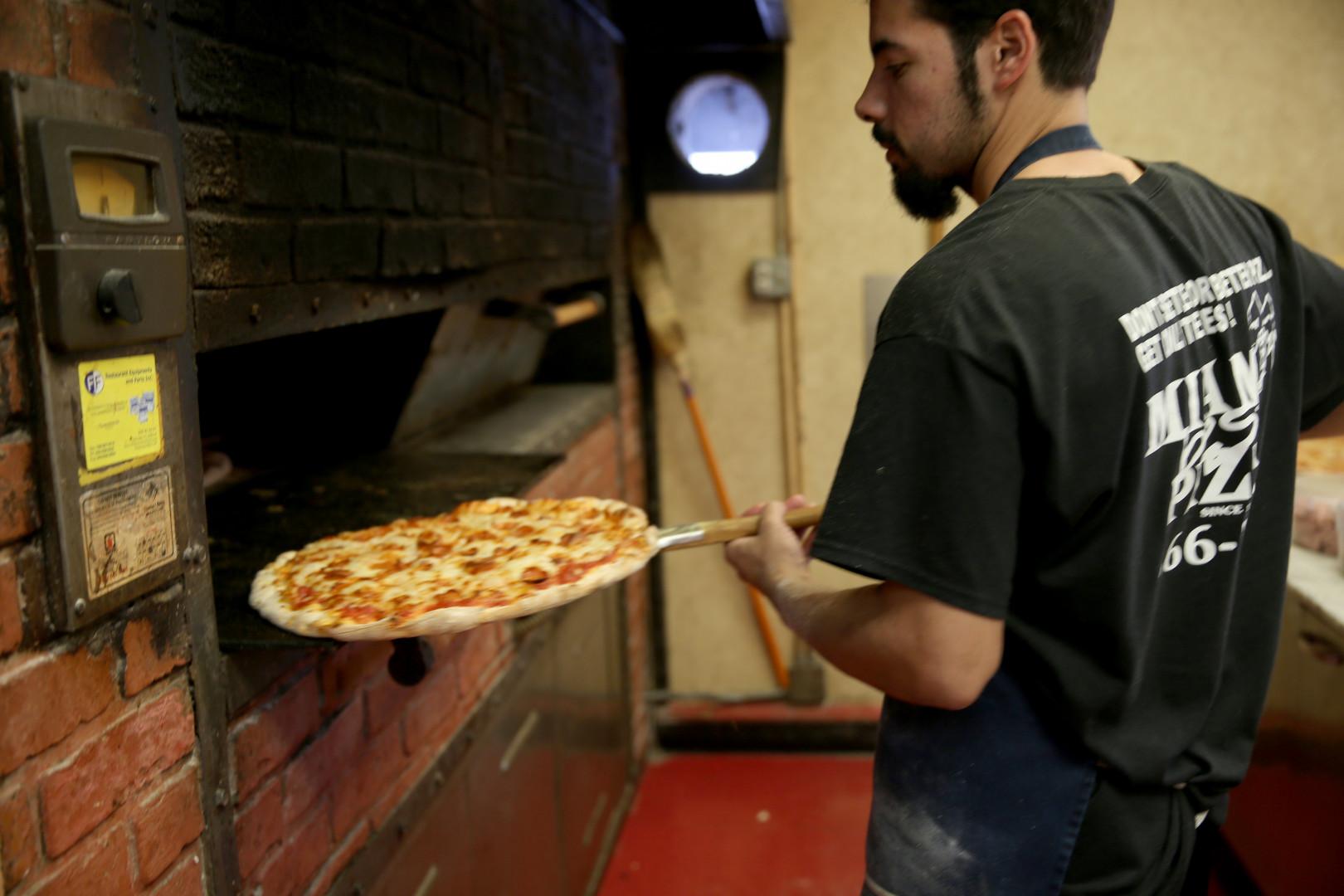Un homme prépare une pizza