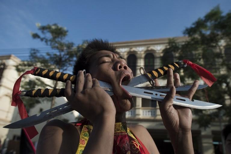 Ce partisant du temple de Jui Tui se transperce les joues avec des couteaux au Festival de Phuket