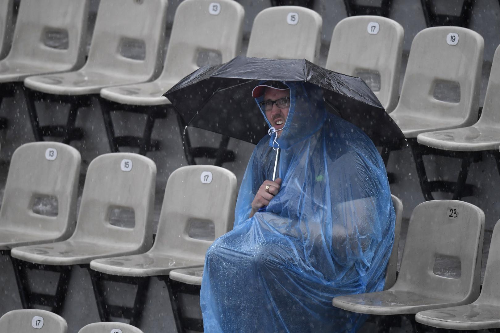 Un spectateur de Roland Garros en cape de pluie assiste au match entre Serena Williams et Alizée Cornet le 28 mai 2016.