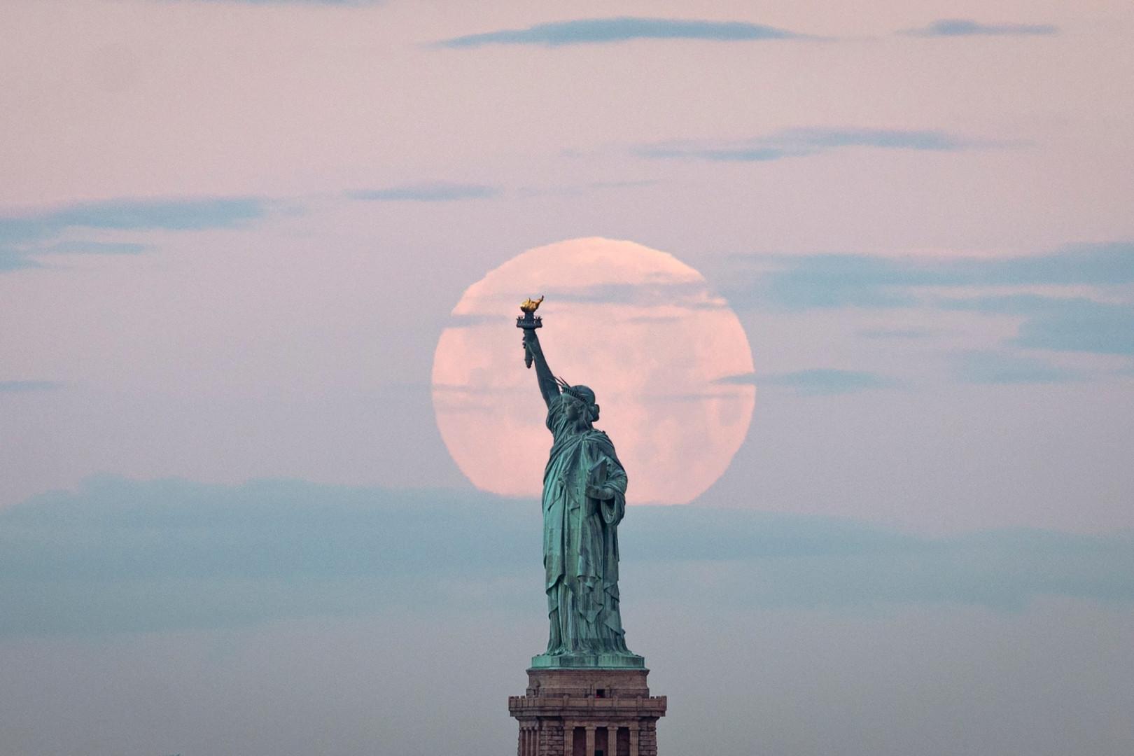 """La dernière """"super Lune"""" de l'année se couche derrière la Statue de la Liberté le 7 mai 2020 à New York."""