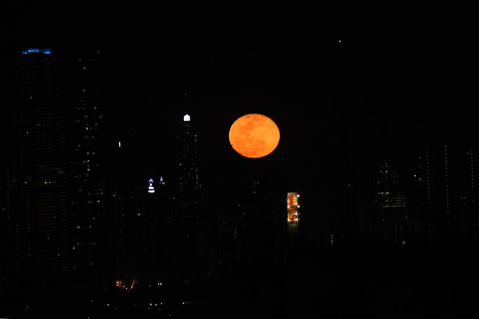 """La """"super Lune"""" se lève au-dessus des bâtiments à Manille, aux Philippines, le 8 mai 2020"""