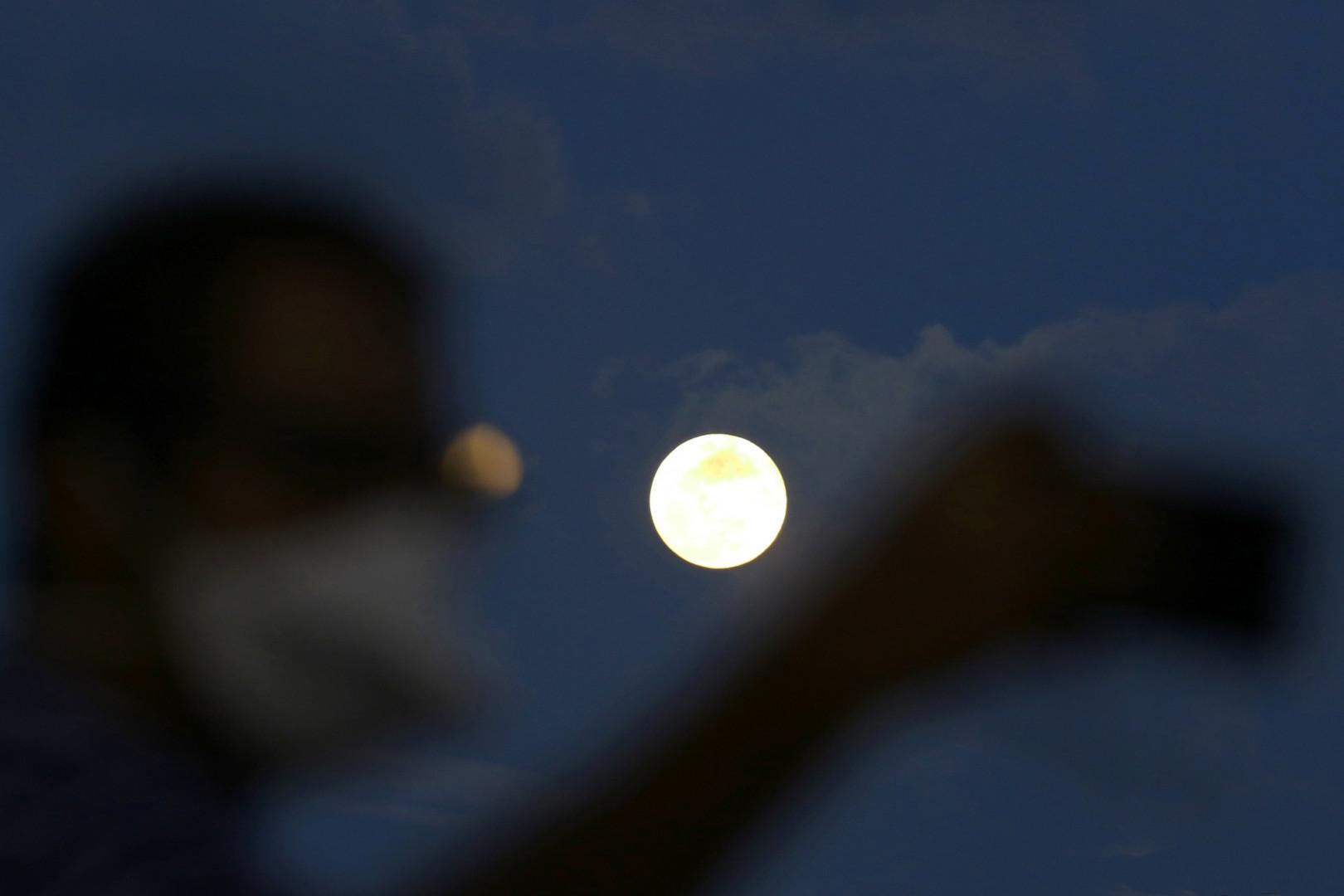 Un homme prend un selfie devant la pleine lune pendant l'éclipse pénombrale à Colombo, au Sri Lanka.