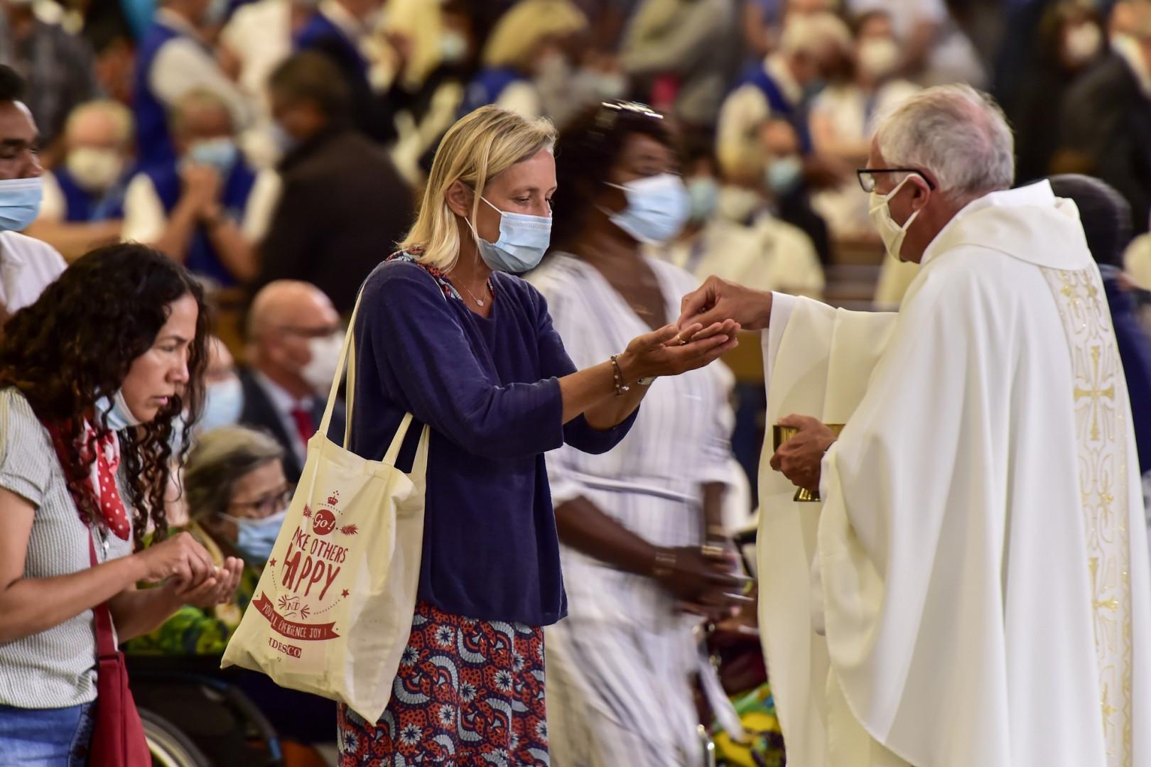 Des fidèles masqués assistent à la messe dominicale devant un nombre réduit de fidèles en raison des mesures sanitaires.