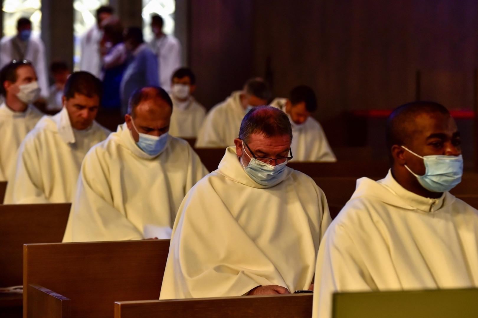 Des prêtres portent des masques assistent à la messe dominicale.