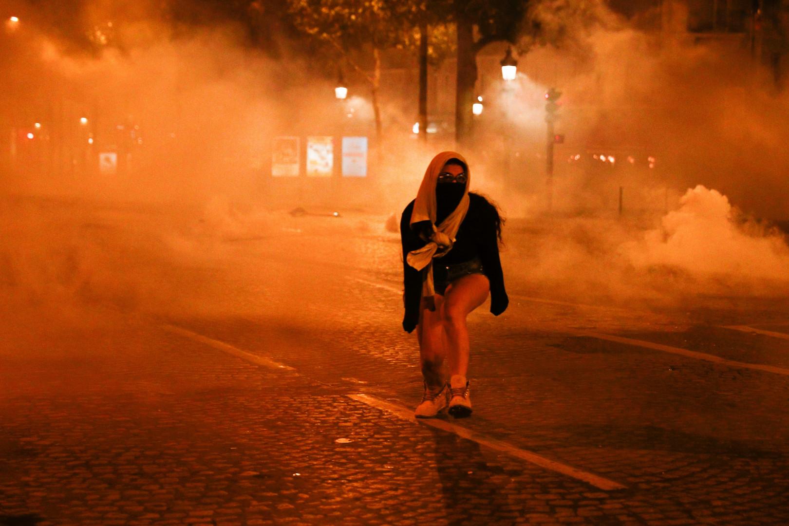 Une femme fuit les gaz lacrymogènes