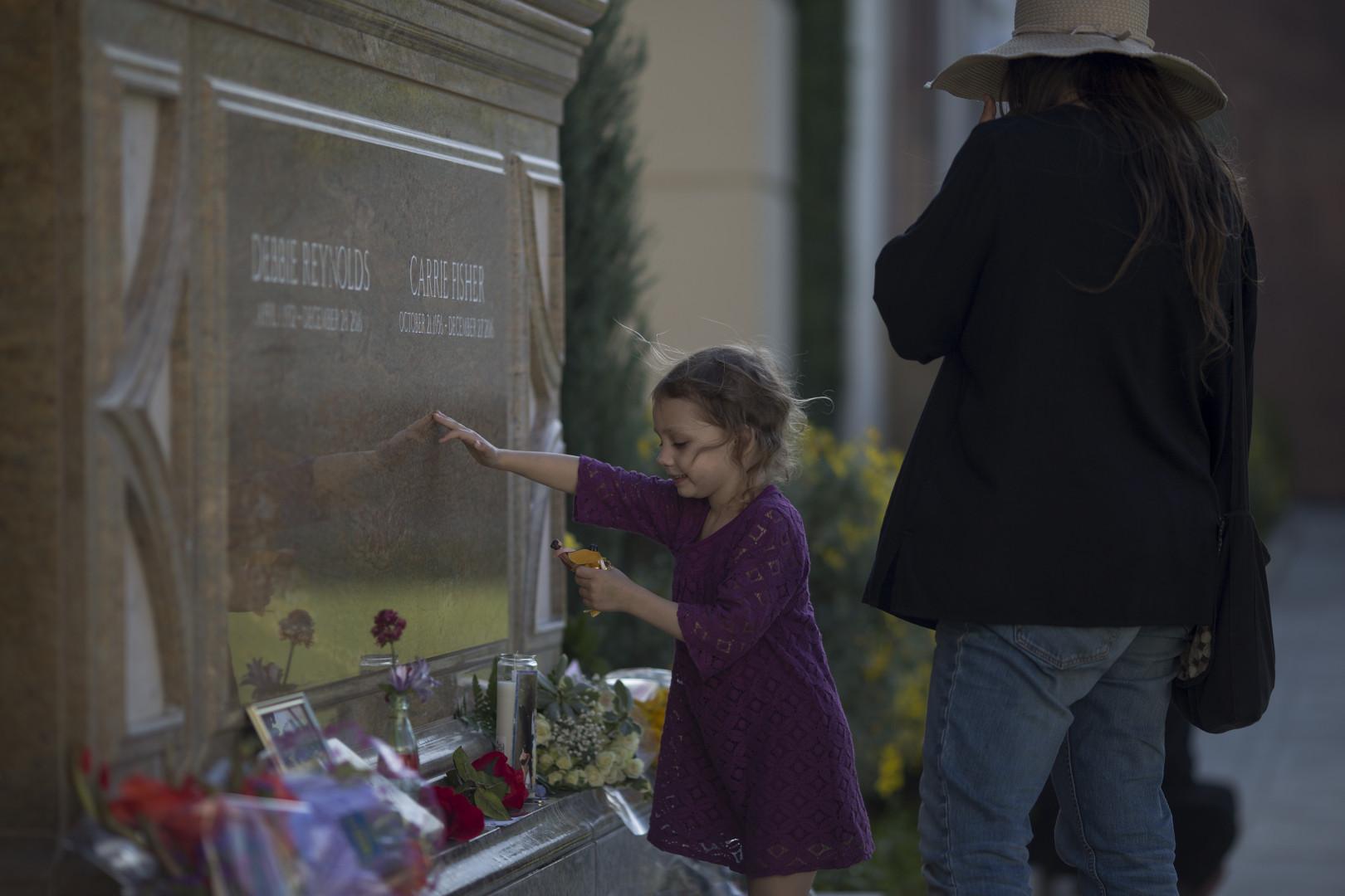 Une fillette dépose des fleurs devant le mémorial consacré aux deux actrices