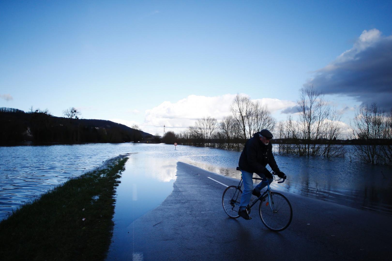Un homme roule à vélo près de la Seine en crue à Cléon (Seine-Maritime) le 1er février