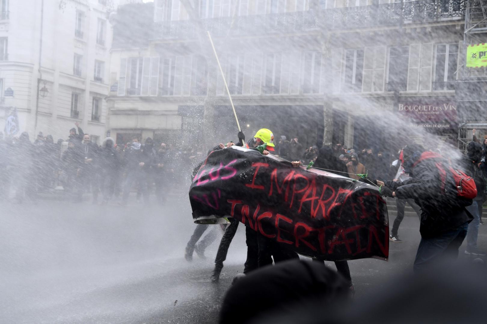 Les policiers répliquent avec des canons à eau face à des manifestants lors de la manifestation du 22 mars à Paris
