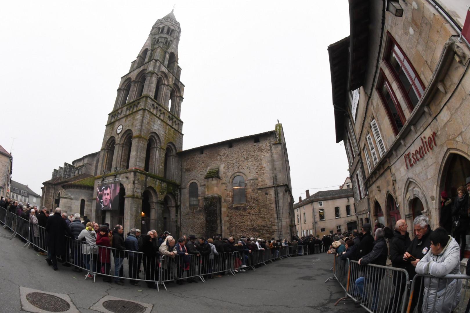 Des gens attendent en dehors de l'église où ont lieu les obsèques de Raymond Poulidor, le 19 novembre