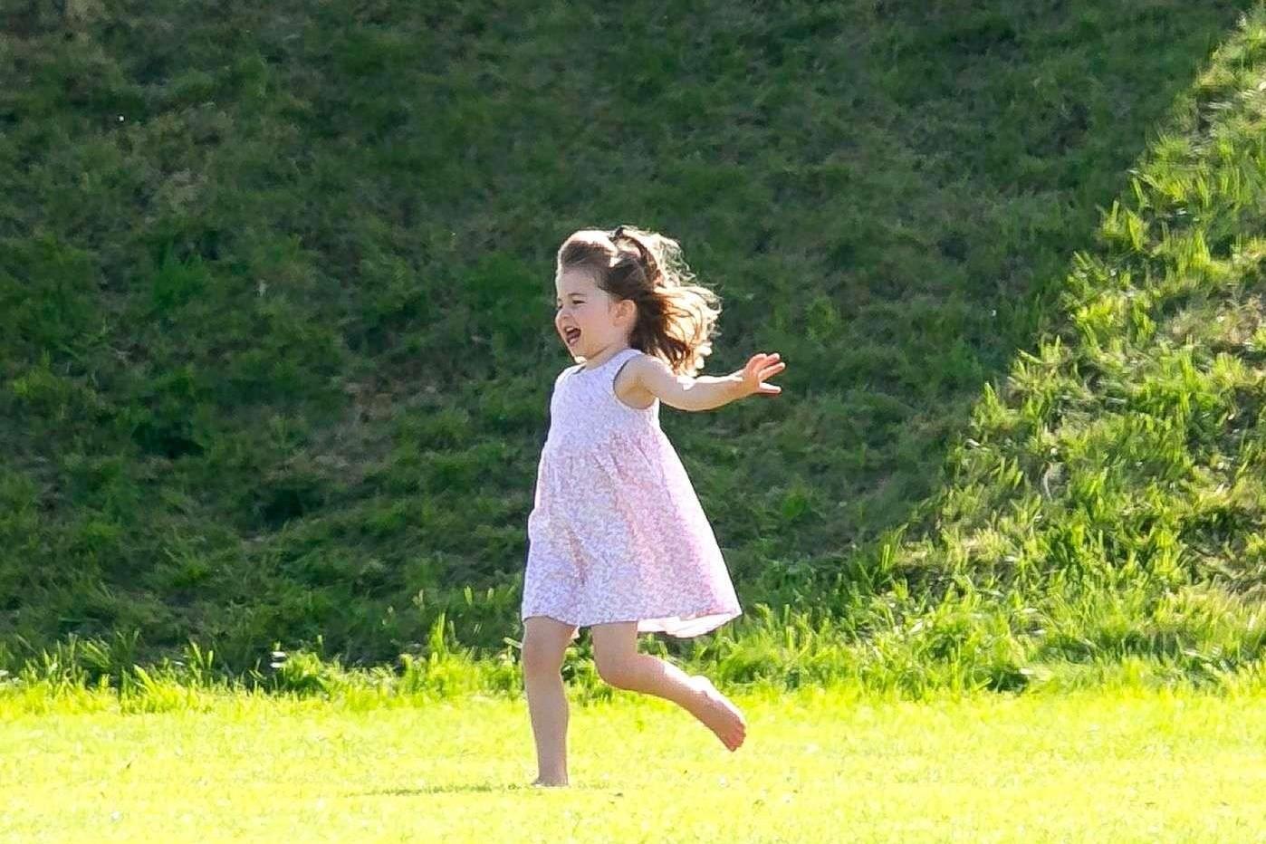 La princesse Charlotte gambade les cheveux dans le vent sur la pelouse