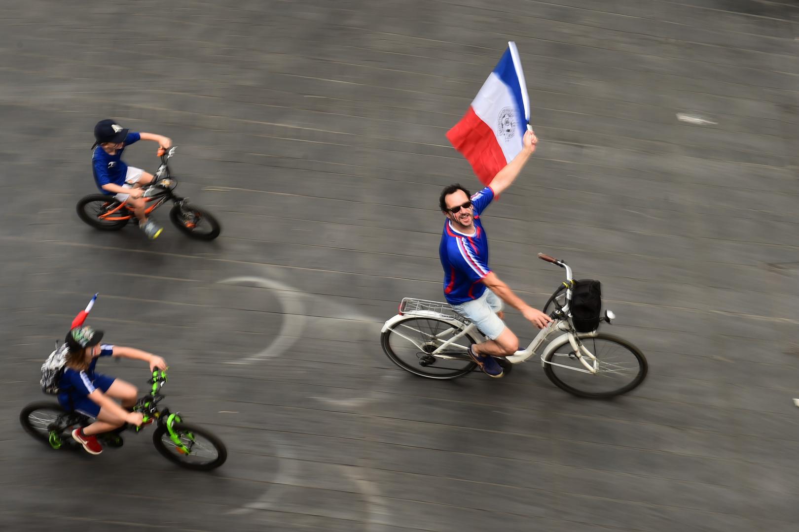 À Bordeaux, même à vélo, les supporters des Bleus ont leur drapeau bleu blanc rouge, le 15 juillet 2018, avant la finale France-Croatie.