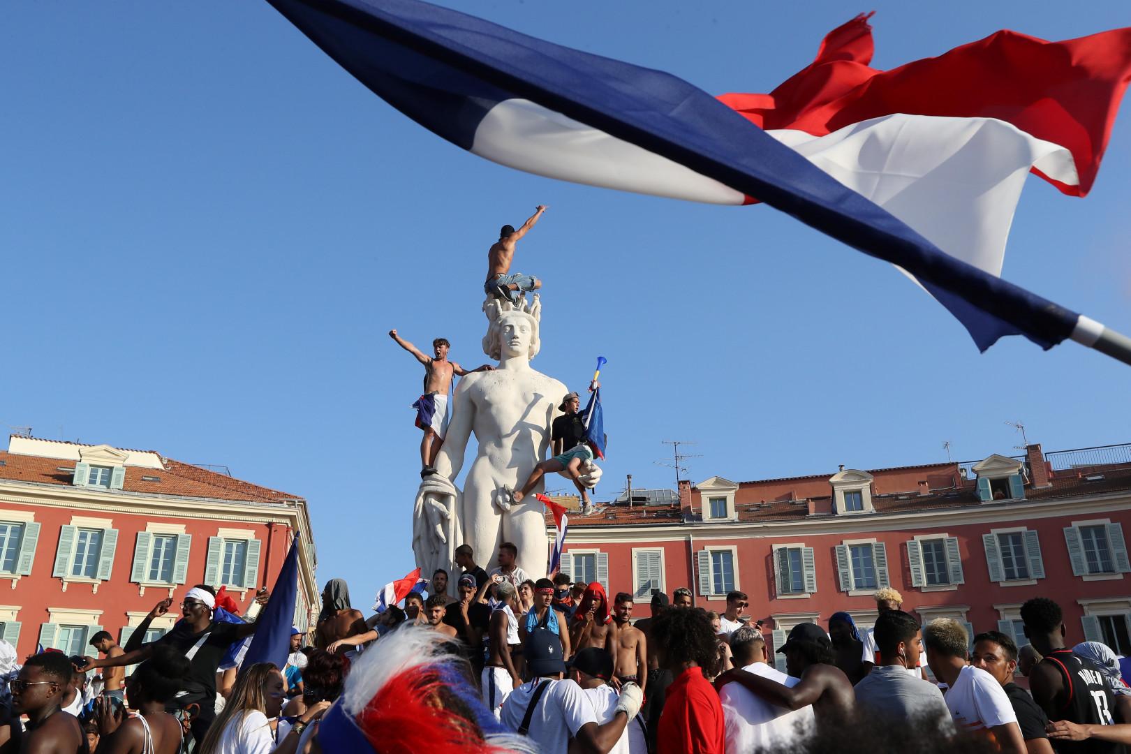 Des supporters montent sur la statue de la place Masséna à Nice le 15 juillet 2018