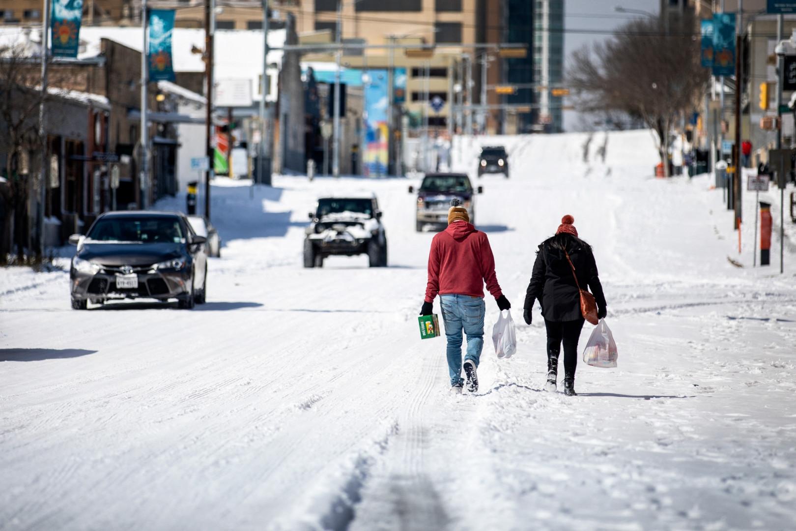 Des gens portent des provisions depuis une station-service le 15 février 2021 à Austin, Texas.