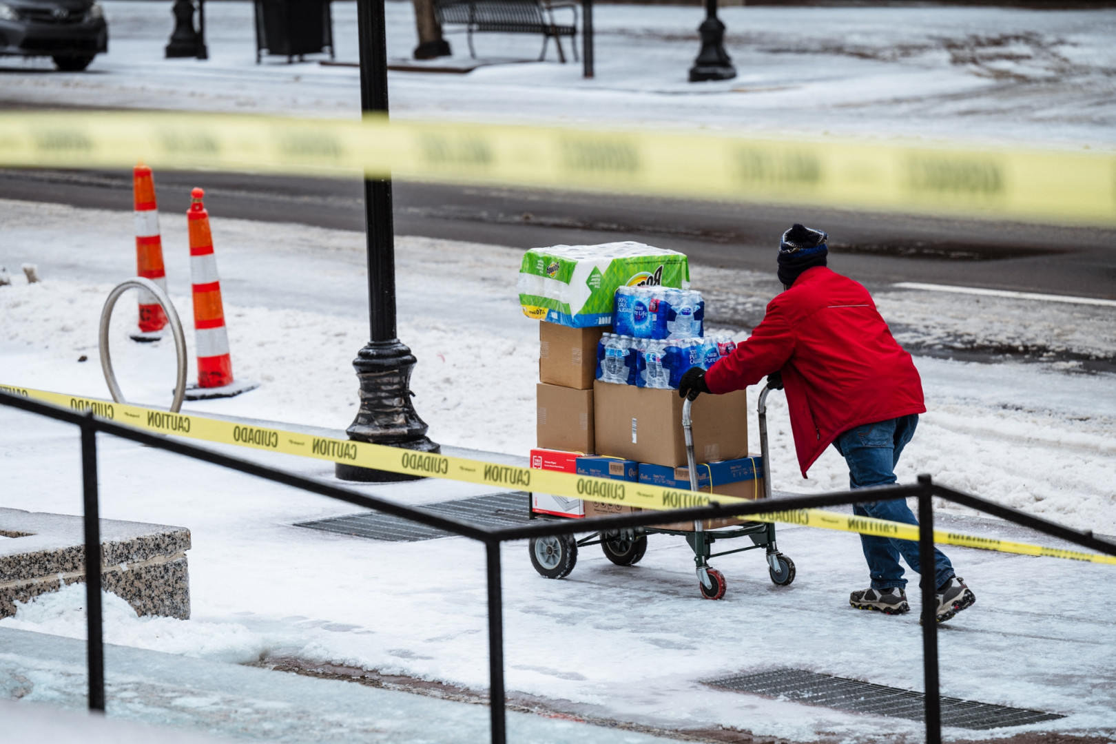 Un livreur pousse un chariot sur un trottoir glacé le 11 février 2021 à Louisville, Kentucky