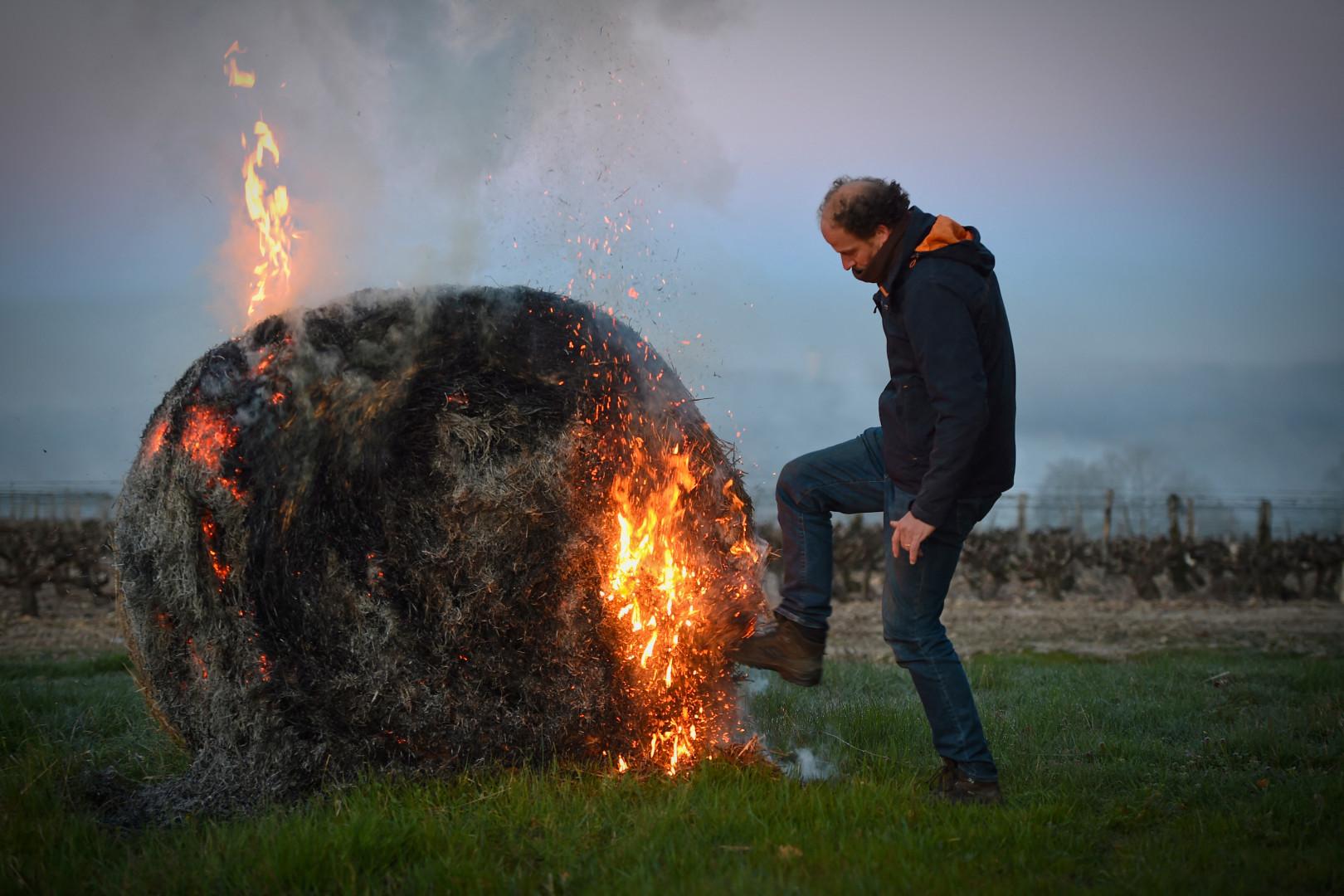 Un viticulteur en train de mettre le feu à une botte de foin pour protéger ses vignes du froid, à Chançay (Indre-et-Loire), le 6 avril 2021