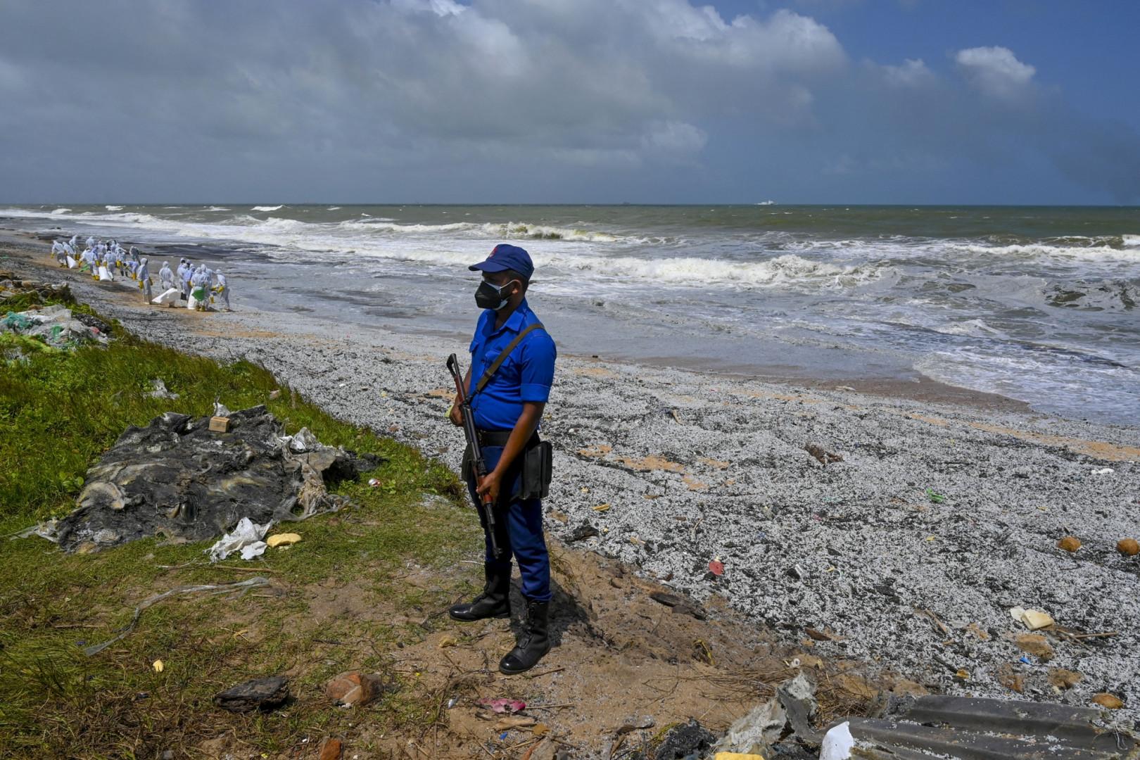 Un personnel de sécurité monte la garde alors que des soldats de la marine srilankaise s'efforcent de retirer les débris répandus par le porte-conteneurs MV X-Press Pearl en feu depuis 10 jours au large du Sri Lanka.