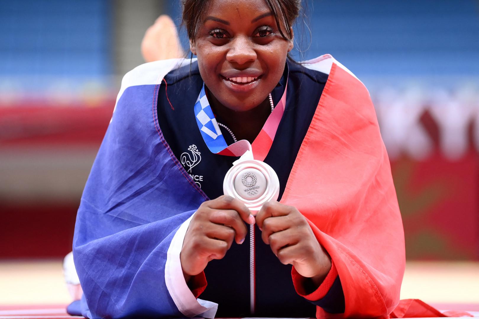 Madeleine Malonga, drapeau français sur ses épaules, montre sa médaille le 29 juillet 2021 à Tokyo.