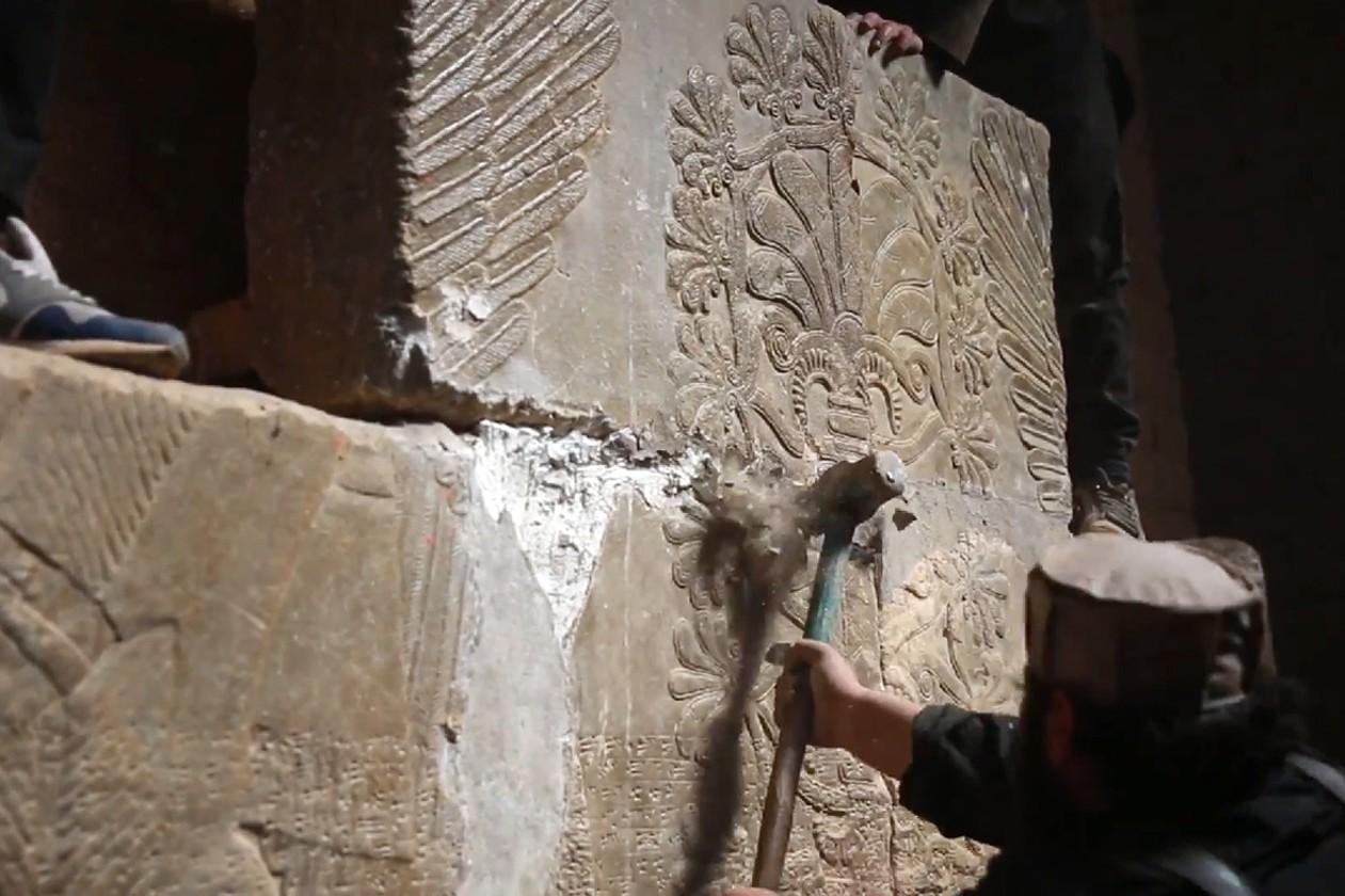Des membres de l'État islamique en train de détruire des dalles de l'ancienne cité assyrienne de Nimroud, en Irak, en 2015