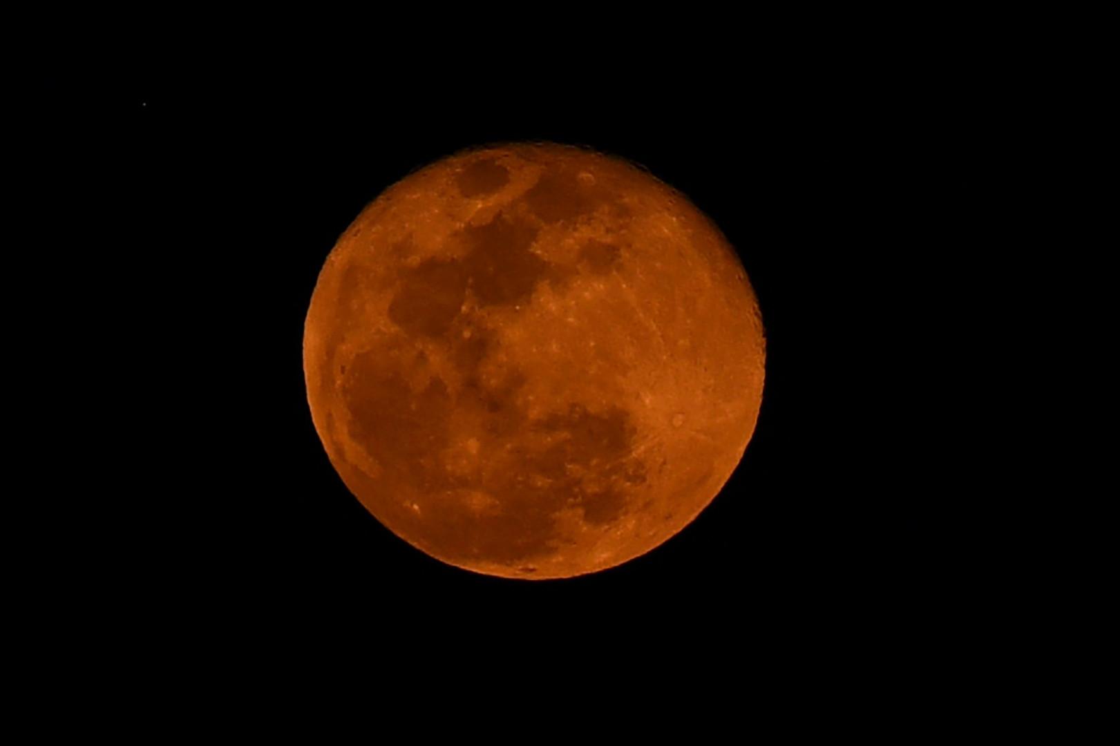 """La """"super Lune"""" vue d'un bâtiment à Manille, aux Philippines, le 8 mai 2020."""