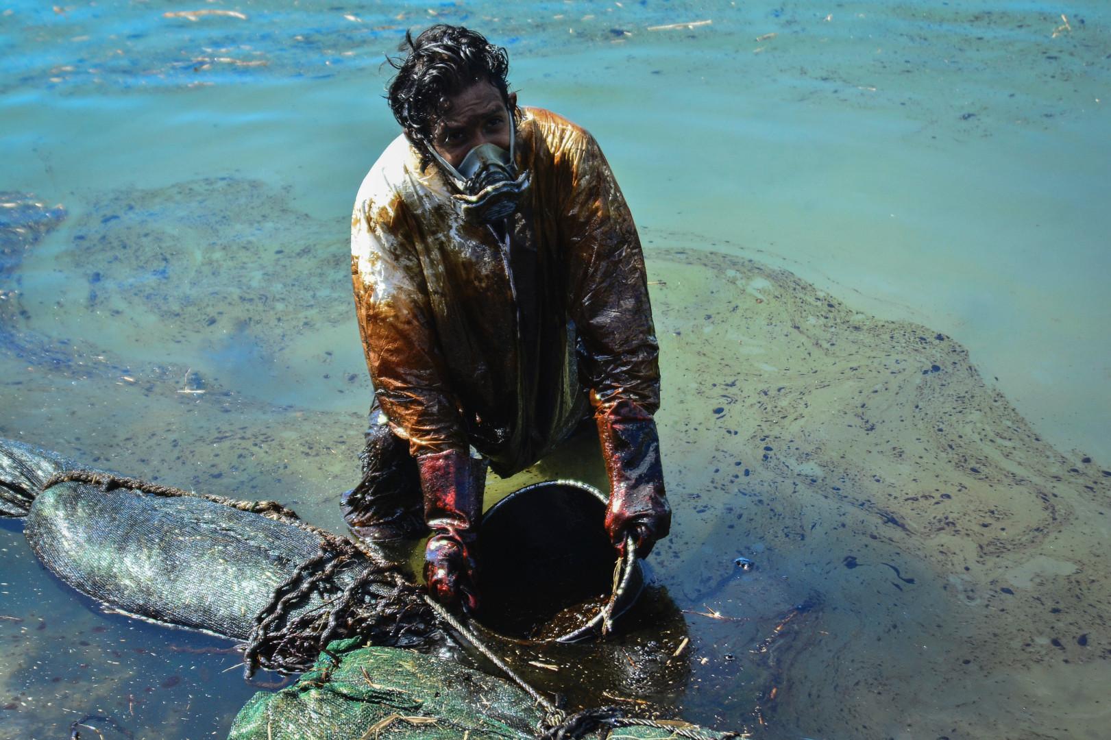Un volontaire tente de ramasser les carburants à la surface, le 08 août 2020
