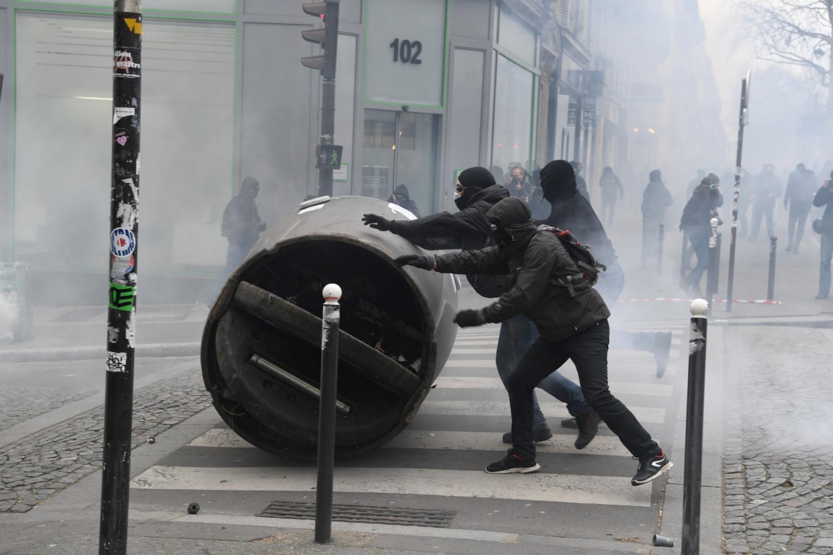 Des personnes cagoulées déplacent un conteneur de verre lors de la manifestation du 22 mars à Paris