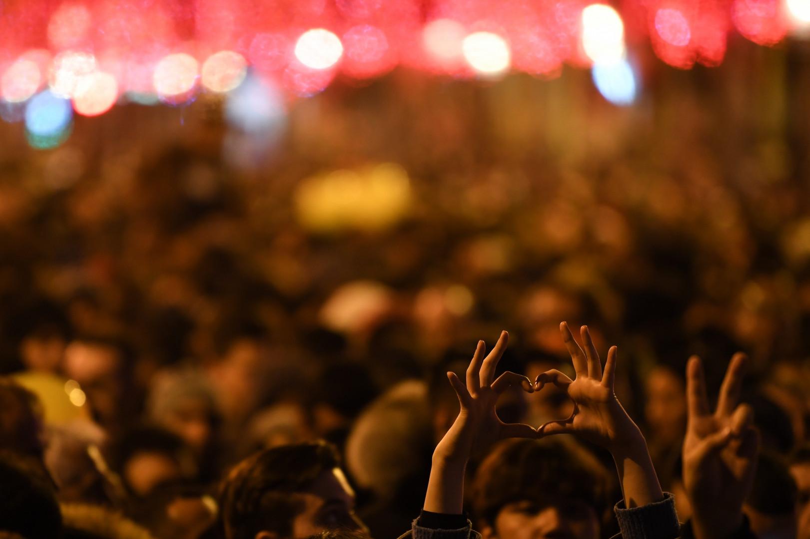 Un cœur formé avec des doigts dans la foule sur les Champs-Élysées, le 31 décembre 2018