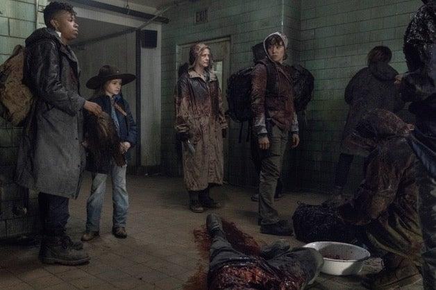 Les survivants prêts à traverser les zombies avec leurs affaires souillées de sang