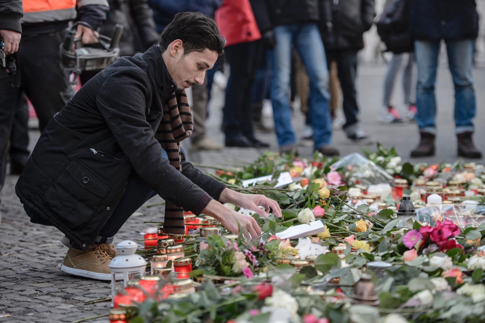 Un réfugié irakien dépose des fleurs devant le mémorial en hommage aux victimes de l'attentat de Berlin, le 19 décembre.
