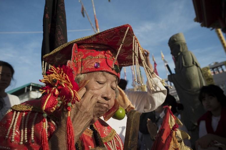 Une fidèle du temple de Jui Tui se perce la joue au Festival de Phuket