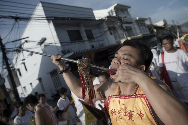 Un dévoué au temple de Jui Tui se coupe la langue avec un lame tranchante au Festival de Phuket