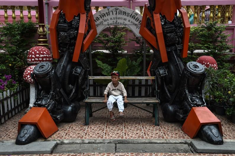 Un petit garçon assis sous une statue géante en métal, Transformers, par Ban Hun Lek metalworks, au temple bouddhiste de Wat Tha Kien à Nonthaburi